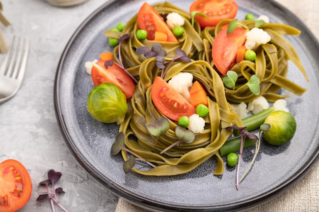 Tagliatelle groene spinazie pasta met tomaat, erwt en microgroene spruitjes Premium Foto