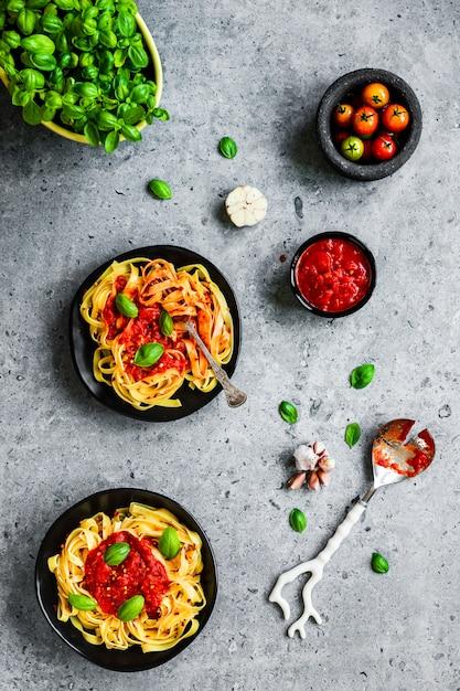 Tagliatelle-pasta met arrabbiatasaus, basilicum, knoflook en cherrytomaatjes Premium Foto
