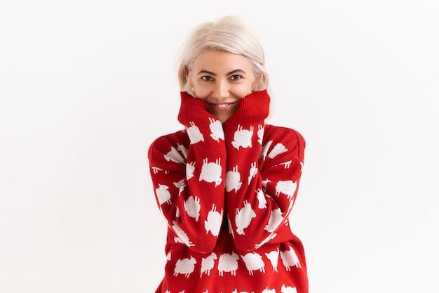 Taille afbeelding van aantrekkelijke charmante tienermeisje met geverfd haar mouwen van haar favoriete trui uitrekken. schattige jonge vrouw gekleed in trui met vriendelijke positieve gezichtsuitdrukking Gratis Foto