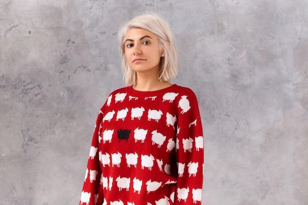 Taille afbeelding van trendy jonge vrouw met geverfd rommelig bob kapsel poseren in rode trui met witte lammeren, geïsoleerd op blinde muur met copyspace voor uw reclametekst of informatie Gratis Foto