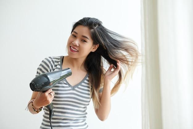 Taille omhoog geschoten van aziatisch meisje die haar haar thuis föhnen Gratis Foto