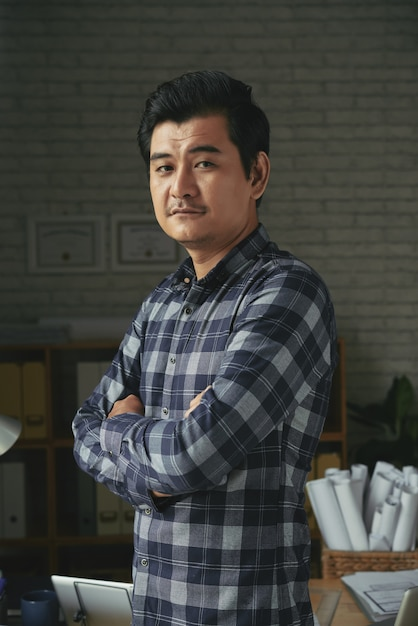 Taille omhoog geschoten van aziatische mensen bevindende die wapens in een architectenbureau worden gevouwen Gratis Foto