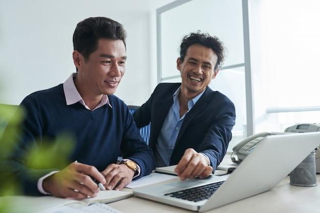 Taille omhoog geschoten van bedrijfsmensen die op het net op laptop surfen Gratis Foto