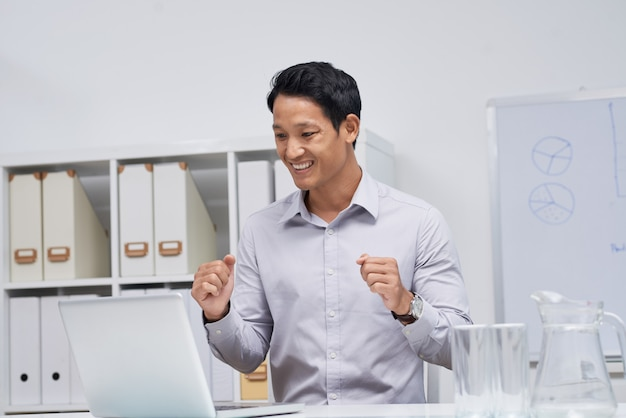 Taille op portret van aziatische zakenmanzitting bij bureau die laptop het scherm bekijken Gratis Foto