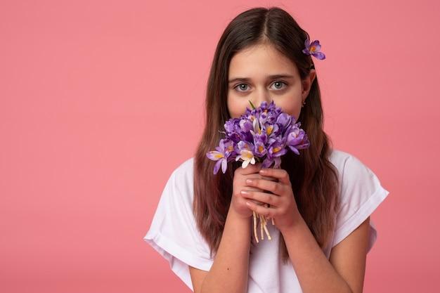 Taille portret van een mooie brunette meisje in wit t-shirt die haar gezicht met paarse lentebloemen verbergen Premium Foto