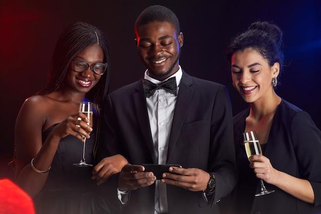 Taille portret van een multi-etnische groep vrienden smartphonescherm kijken tijdens een elegant feest Premium Foto