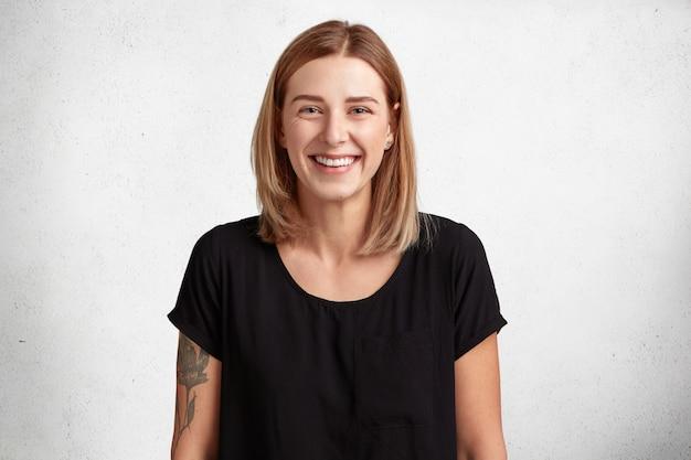 Taille portret van mooie lachende jonge vrouw met positieve uitdrukking, draagt casual zwart t-shirt, arm heeft getatoeëerd, modellen tegen betonnen muur Gratis Foto