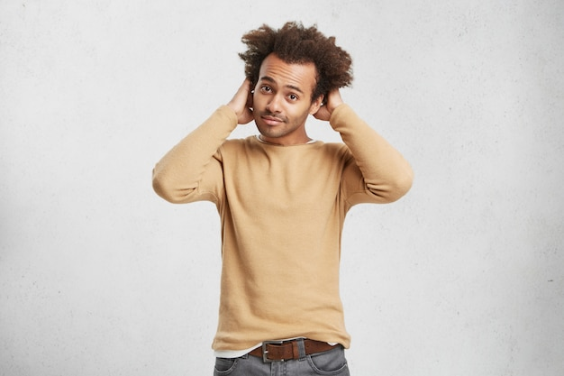 Taille portret van stijlvolle krullend aantrekkelijke man met donkere huid draagt modieuze kleding Gratis Foto