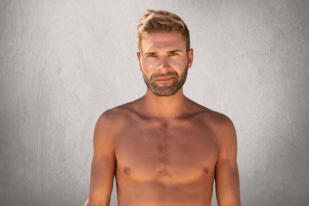 Taille portret van topless ongeschoren jonge man met een sterk lichaam staande tegen een grijze achtergrond Gratis Foto