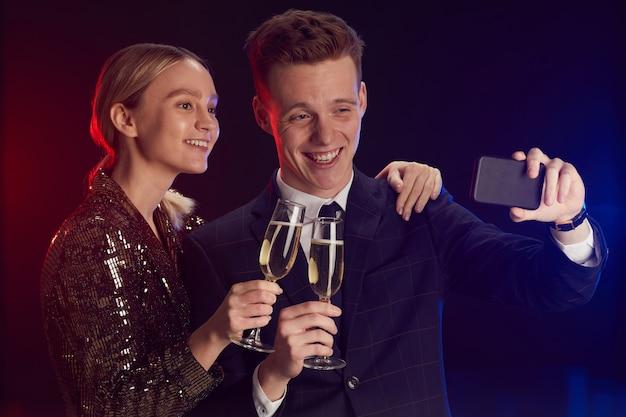 Taille-up portret van een jong koppel selfie foto nemen via smartphone terwijl u geniet van feest op prom night staande tegen gebrek achtergrond Premium Foto