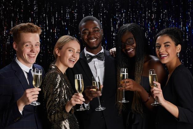 Taille-up portret van een multi-etnische groep vrienden die champagneglazen houden en glimlachen naar de camera terwijl u geniet van een elegante partij Premium Foto
