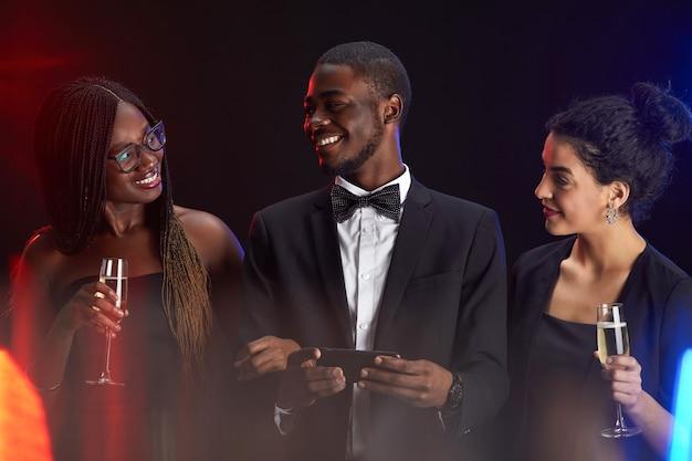 Taille-up portret van een multi-etnische groep vrienden die gelukkig glimlachen terwijl u geniet van een elegant feest Premium Foto