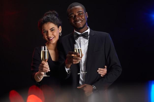 Taille-up portret van elegant gemengd ras paar champagne glas houden en glimlachen naar de camera terwijl staande tegen een zwarte achtergrond op feestje, kopieer ruimte Premium Foto