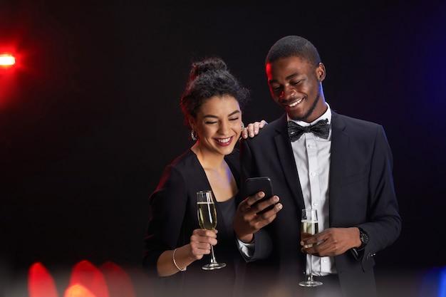 Taille-up portret van elegant gemengd ras paar met smartphone en champagneglazen terwijl staande tegen zwarte achtergrond op feestje, kopieer ruimte Premium Foto