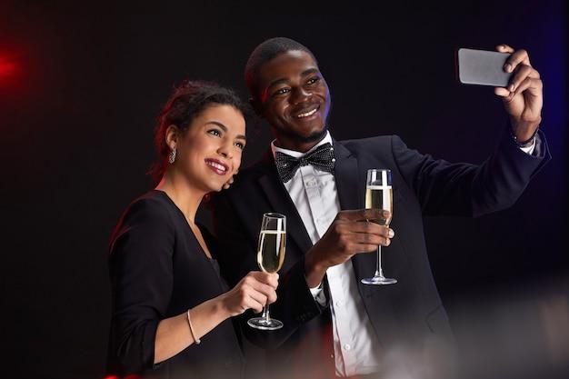 Taille-up portret van elegant gemengd ras paar selfie foto terwijl staande tegen een zwarte achtergrond op feestje, kopie ruimte Premium Foto