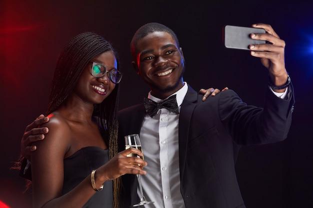 Taille-up portret van elegante afro-amerikaanse paar selfie foto nemen terwijl u geniet van feest Premium Foto