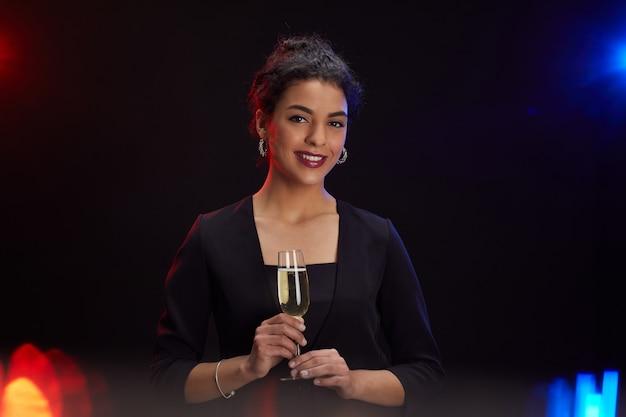 Taille-up portret van elegante midden-oosterse vrouw met champagne glas en lachend naar de camera terwijl staande tegen een zwarte achtergrond op feestje, kopieer ruimte Premium Foto