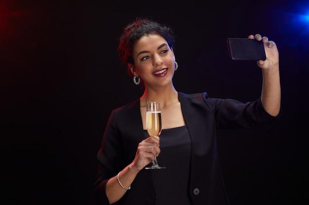 Taille-up portret van elegante midden-oosterse vrouw met champagneglas en selfie foto nemen terwijl staande tegen zwarte achtergrond op feestje, kopieer ruimte Premium Foto