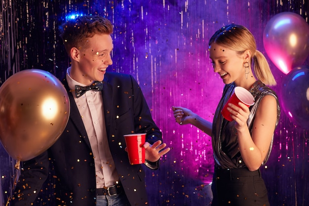 Taille-up portret van gelukkige tiener paar dansen in ingerichte hal en rode cups te houden terwijl u geniet van prom night of feest Premium Foto