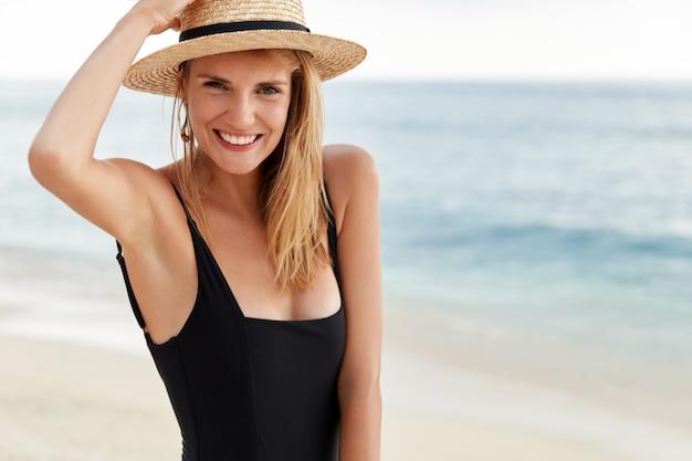 Taille-up portret van jonge schattige vrouwelijke reiziger in bikini en hoed ontdekt tropisch land, poseert aan de kustlijn van de oceaan, blij om zomervakantie in het buitenland door te brengen, heeft een positieve mooie uitdrukking. Gratis Foto