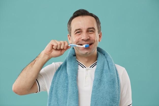 Taille-up portret van lachende man van middelbare leeftijd tanden poetsen Premium Foto
