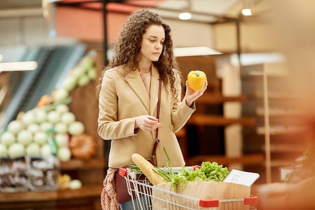 Taille-up portret van moderne jonge vrouw met paprika tijdens het kiezen van verse groenten en fruit op boerenmarkt Premium Foto