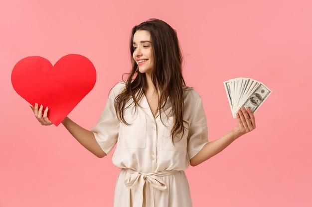 Taille-up portret verrast en vastberaden brunette vrouw maakt haar keuze voor ware liefde, kijkend naar het hart, met valentijns kaart en contant geld, schelen rijkdom en geld, roze muur Premium Foto