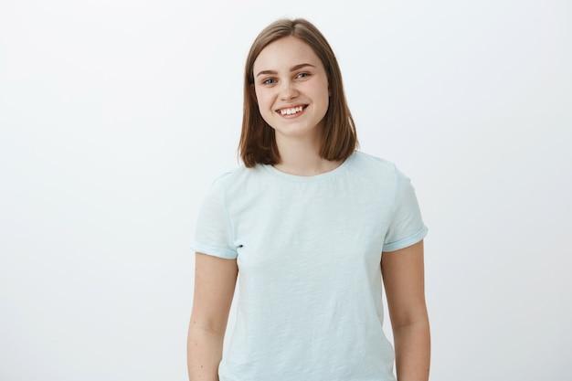Taille-up shot van ambitieuze vrolijke en schattige vrouwelijke brunette in trendy t-shirt glimlachend vreugdevol verheugd en tevreden terwijl felicitaties ontvangen voor het winnen van prijs over witte muur Gratis Foto