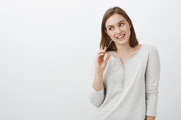 Taille-up shot van creatieve energieke en gelukkige europese vrouw met kort bruin kapsel bijtende rand van brillen met bril in hoofd kantelend hoofd van interesse starend opgetogen en geïntrigeerd links Gratis Foto
