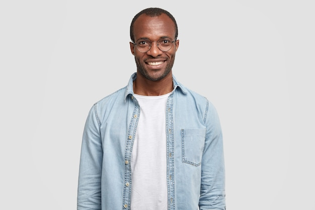 Taille-up shot van knappe zelfverzekerde vrolijke mannelijke ondernemer heeft een brede glimlach Gratis Foto