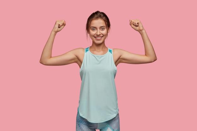 Taille-up shot van sportieve vrouw steekt hand op om haar spieren te tonen Gratis Foto
