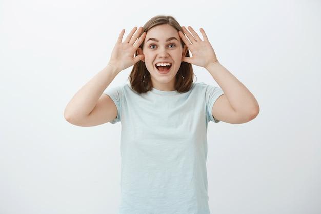 Taille-up shot van verrast en tevreden vrouw kan niet geloven dat ze de reis heeft gewonnen door deel te nemen aan een wedstrijd met de handpalmen in de buurt van het gezicht glimlachend breed en opgewonden starend met een dromerige opgetogen blik Gratis Foto