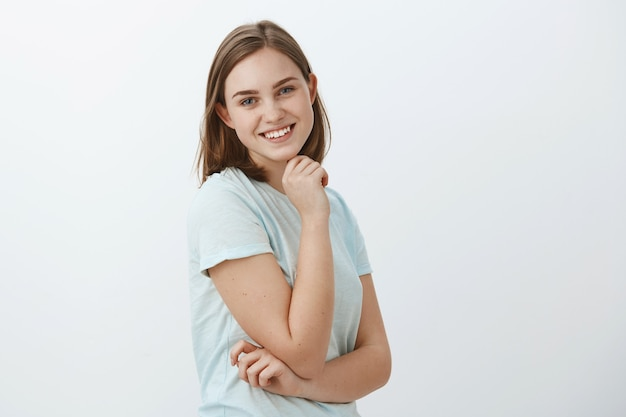Taille-up shot van vriendelijk ogende vrolijke gelukkige meisje met bruin kort kapsel staande in profiel hand op de wang vasthouden en draaien met brede gelukkige glimlach poseren tegen grijze muur Gratis Foto