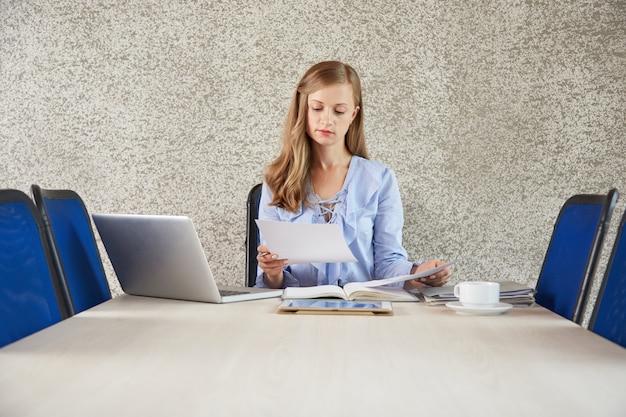 Taille van jonge bedrijfsdamezitting bij bureau in het bureau dat het document bekijkt Gratis Foto