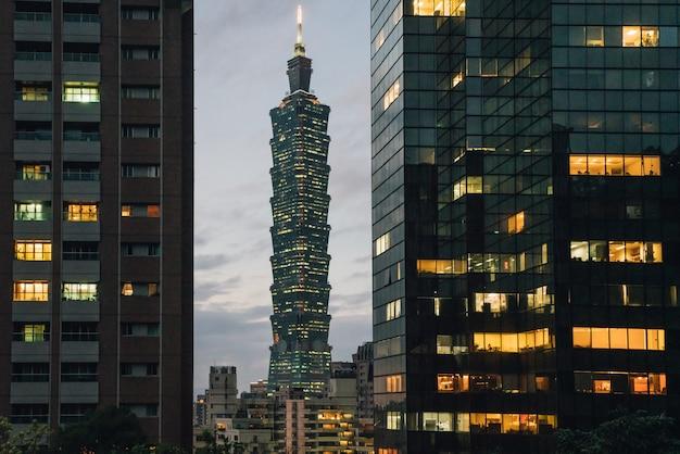 Taipei 101 wolkenkrabber in de schemering met commerciële gebouwen op de voorgrond. Premium Foto
