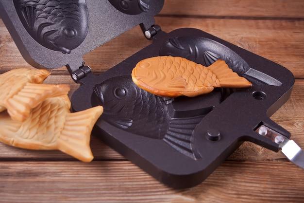Taiyaki japanse straatvoedsel vis-vormige zoete vullende wafel op hout Premium Foto