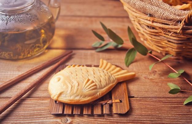 Taiyaki japanse straatvoedsel vis-vormige zoete vullende wafel op houten lijst Premium Foto