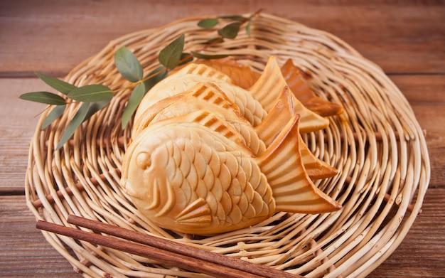 Taiyaki japanse straatvoedsel vis-vormige zoete vullende wafel op houten lijst. Premium Foto