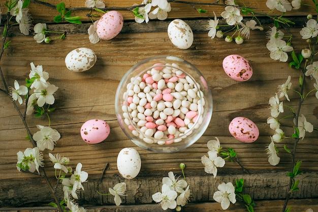 Tak van lentebloemen en kleurrijke roze snoep eieren voor pasen op rustieke Gratis Foto