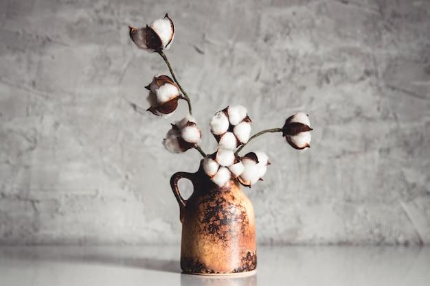 Takken van katoen in een bruine rieten vaas op een achtergrond van een grijsblauwe muur Premium Foto
