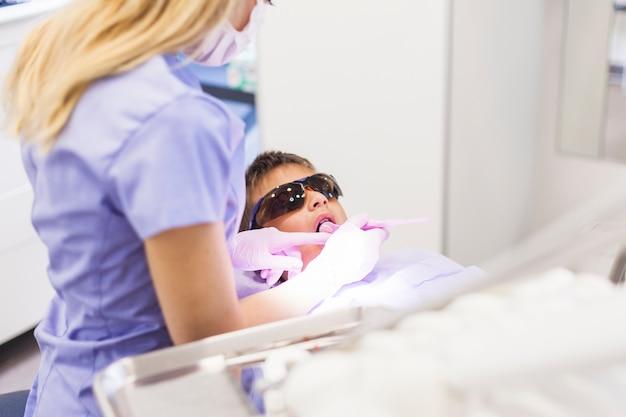 Tandarts die de tanden van de jongen met tandspiegel controleert Gratis Foto