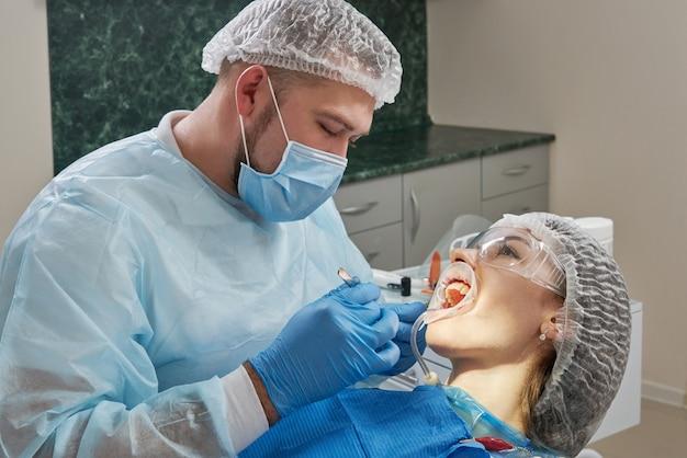 Tandarts die een tandheelkundige behandeling op een vrouwelijke patiënt doet. tandarts die de tanden van een patiënt in modern onderzoekt Premium Foto