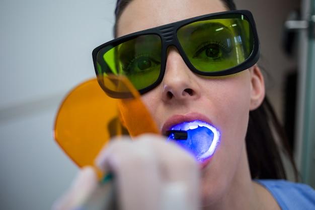 Tandarts die patiëntentanden met tand het genezen licht onderzoeken Gratis Foto