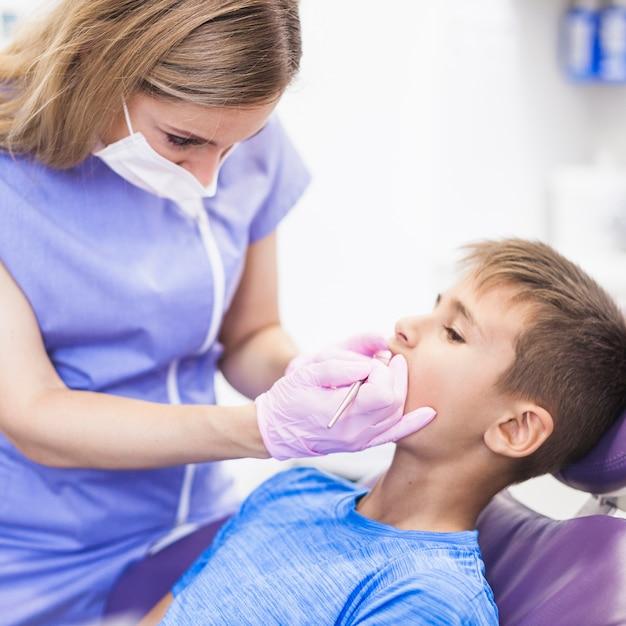 Tandarts die tanden van een jongen in kliniek controleert Gratis Foto