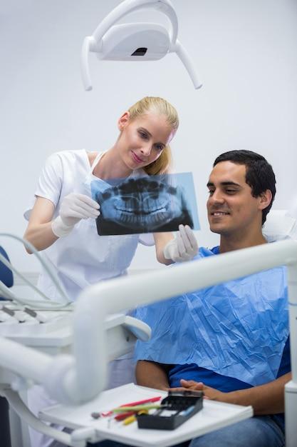 Tandarts die tandröntgenstraal toont aan patiënt Gratis Foto