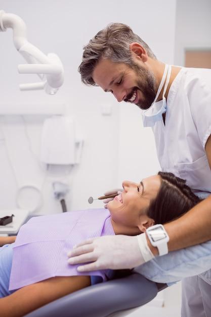 Tandarts die terwijl het onderzoeken van patiënt glimlacht Gratis Foto