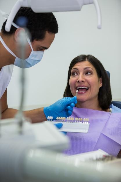Tandarts die vrouwelijke patiënt met tandenschaduwen onderzoeken Gratis Foto