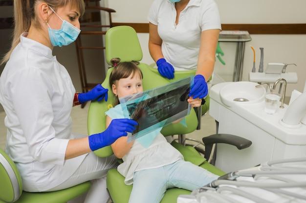 Tandarts en meisje patiënt radiografie kijken Gratis Foto