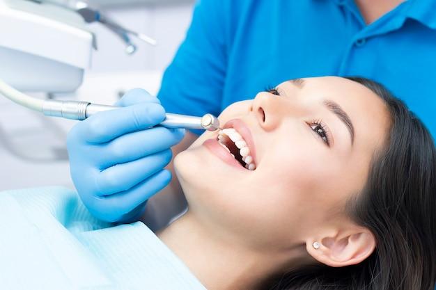 Tandarts en patiënt in de tandartspraktijk. vrouw die tanden heeft die door tandartsen worden onderzocht Premium Foto