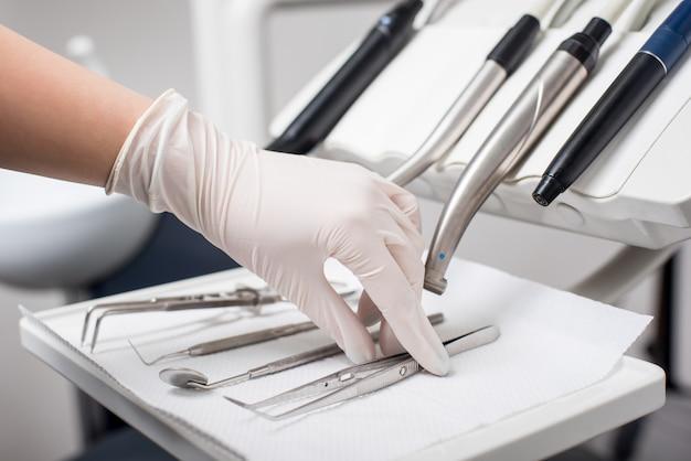 Tandarts met gehandschoende hand plukt tandheelkundige pincet in tandheelkundige kantoor. close-up, selectieve aandacht. tandheelkunde Premium Foto